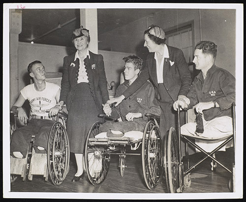 Three white men whose legs have been amputated, with Helen Keller and Polly Thomson. Keller, smiling, touches the hand of the man to her right and holds the hand of the man to her left. The veterans wear military hospital clothing and are using wheelchairs.