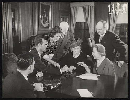 In a wood-paneled room, several white people surround Helen Keller, who sits at a table with her hands on a small device.