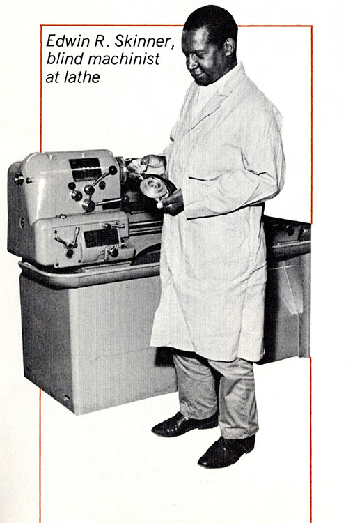 Seen in a laboratory coat, a blind Black man stands in front of a large factory lathe and holds a piece of equipment.