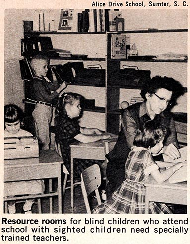 Four young, white school children who are blind study in a resource room. Three girls sit at individual desks. One uses a braille writer, while the other two read braille texts. A white female teacher sits next to one of the girls and helps her read. In the background, a boy selects books from bookshelves.