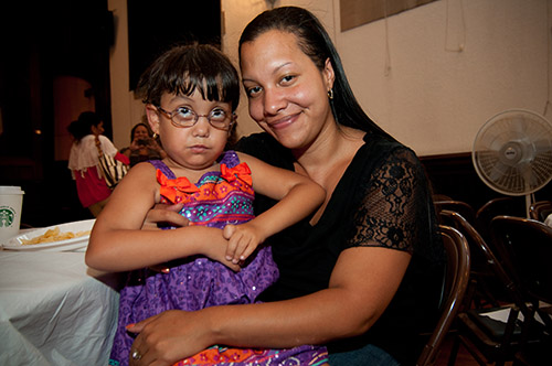 A young Brown girl wearing a purple and orange sleeveless dress with straps sits on a woman's lap. The child wears round glasses and is looking up. The woman smiles at the camera.