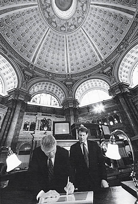 President Clinton, standing, signs the Telecommunications Act in a rotunda with arched windows and a beautifully decorated ceiling. Vice President Al Gore stands behind the President.