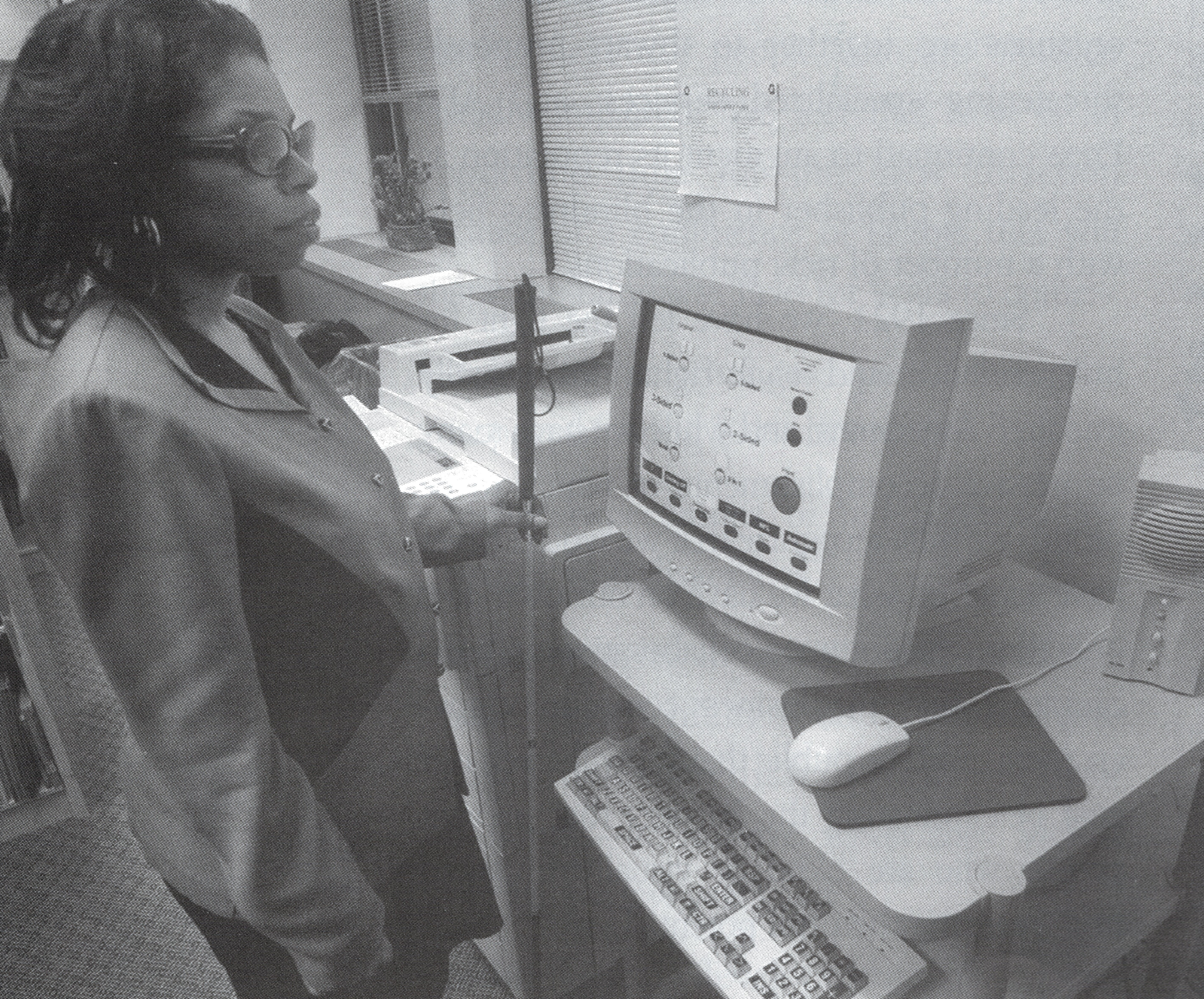 A Black woman wearing dark glasses and holding a cane stands in front of a computer on a desk. Next to her is a copy machine. The computer monitor displays copier settings.