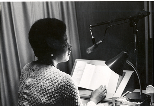 Maya Angelou sits in profile in front of a microphone and table lamp. Her book