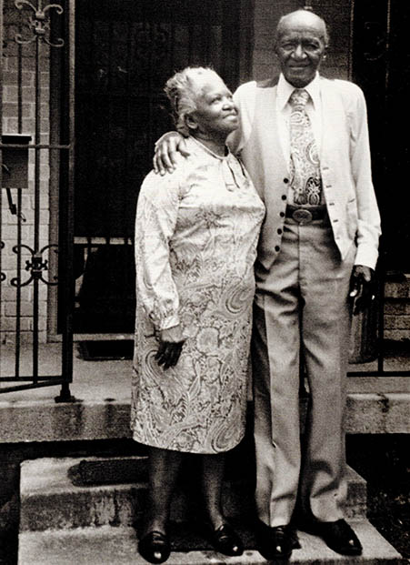An elderly Black couple stand on the stoop outside their home. The couple are smiling. The wife looks up toward her husband, who has his arm around her shoulder.