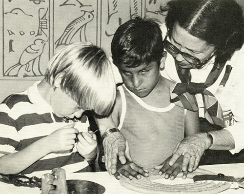 Two boys with visual impairments, one white and one brown, sit at a table that holds a few objects. A white woman stands behind one of the boys, guiding his hands around a circular object. The other boy holds a small object close to his face.