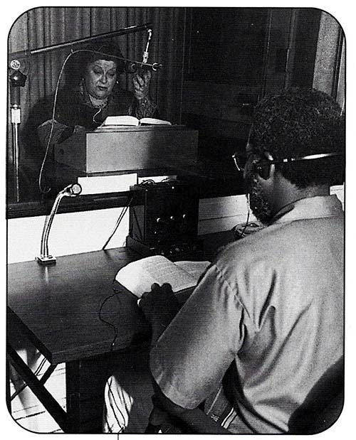 Argentinian narrator, Graciela Lecube sits in a recording studio, behind a glass window, in front of a microphone. A book is open in front of her, propped on a stand. In the foreground, facing Lecube, a Black man sits a desk with a book open. The man wears headphones.