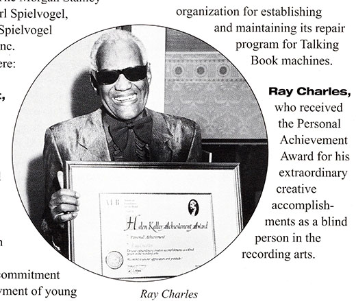Ray Charles holds the Helen Keller Achievement Award, a large framed certifIcate. The certificate bears the AFB logo, an image of Helen Keller, a metallic seal, and two signatures. Charles is smilling and wears dark glasses and a shiny blazer with a large bow tie and matching button-down shirt.