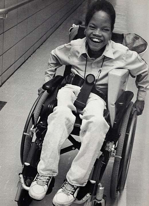 A smiling, young Black child with a visual impairment moves his wheelchair along a hallway.