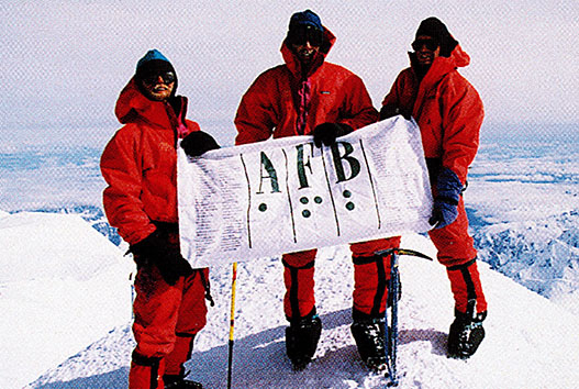 Erik Weihenmayer with three of the other climbers on his team, at the summit of Mt. McKinley, June 27, 1995. They hold the AFB flag, which includes the braille code for the letters A, F, and B.