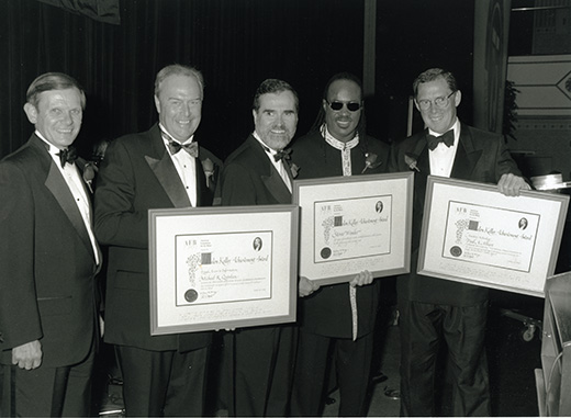 Stevie Wonder, smiling and dressed in formal attire, stands with four white men. The group holds three awards between them.