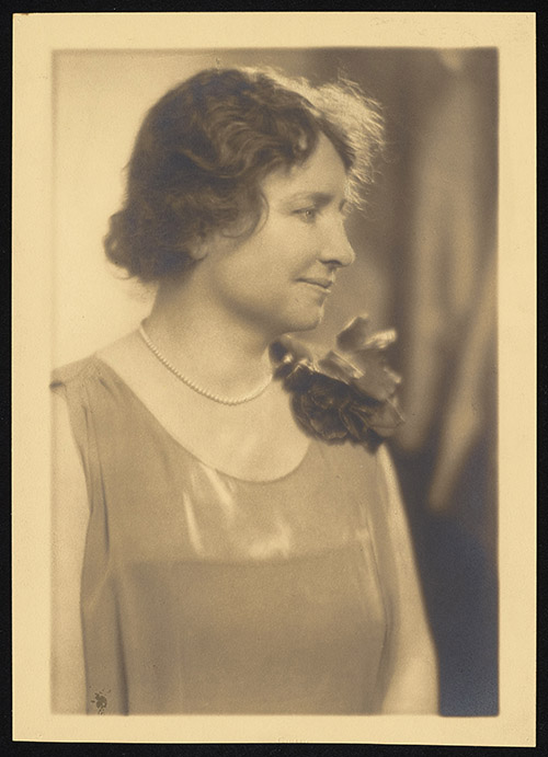 Sepia photograph of a half-length portrait of Helen Keller. Keller smiles gently, her face in profile. She wears a sleeveless boat-neck dress with a flower decoration on her left shoulder and a pearl necklace.