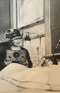 A white child who is blind lies in bed. Helen Keller sits on the far side of the bed, smiling and holding a radio set.