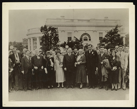 A cluster of over 30 delegates in formal attire stand outside the White House. Most of the visible delegates are white. They stand close together, with serious expressions on their faces.