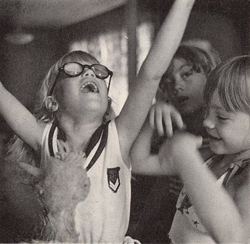 Three young white girls are playing. One girl with glasses has her arms and head raised joyously up towards the ceiling. A second girl is smiling and is in the middle of extending her arms up as well. A stuffed animal is visible in the foreground.