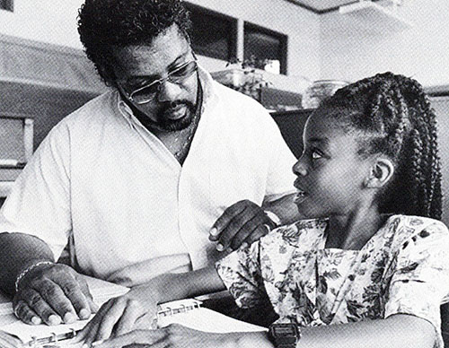 A young Black girl and her father sit side by side as the girl reads braille text on the desk in front of her.