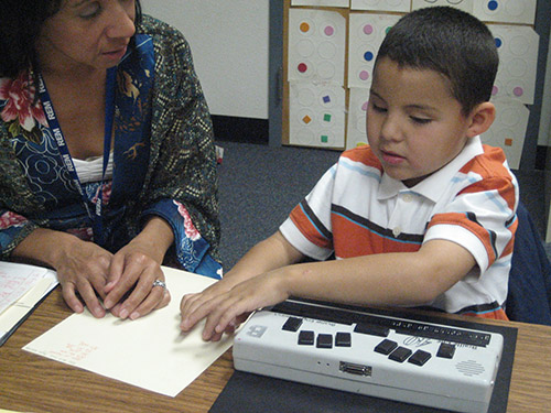 A young boy who is blind and a female teacher sit behind a desk in a classroom. A braille writer is infront of the student. He is reading text in braille that is on the table beside the braille writer. His teacher looks on.