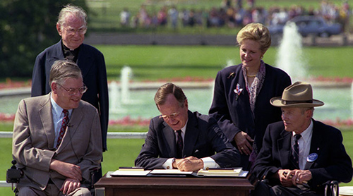 President George H. W. Bush sits at a desk on the South Lawn of the White House. Seated in wheelchairs are Evan Kemp to his right and Justin Dart to his left. Standing behind them are Reverend Harold Wilke and Swift Parrino.
