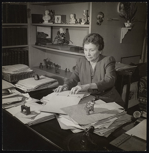 Helen Keller sits at her desk in her home office. She is reading a document in braille. Papers and objects cover the table and books and objects are visible on shelves behind her.