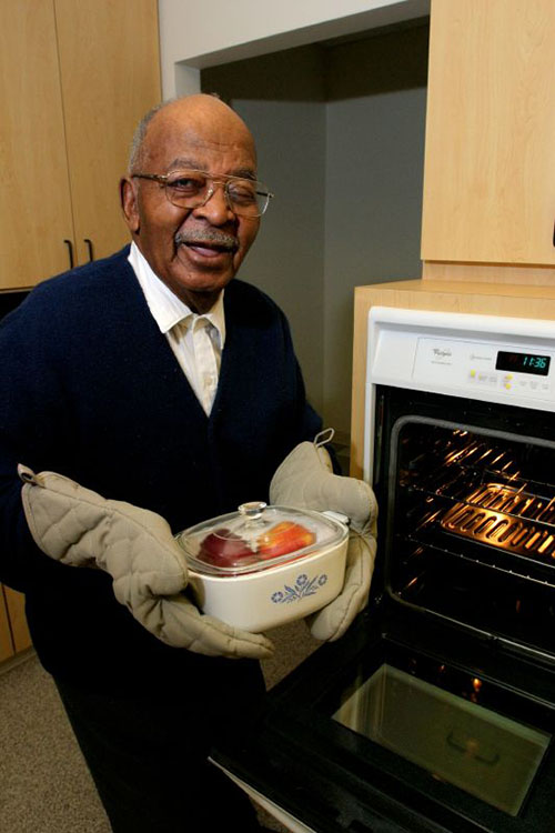 An elderly Black man in a kitchen smiles at the camera as he holds up a square white casserole dish with a clear glass lid in his gloved hands. He stands infront of the open door of an oven.