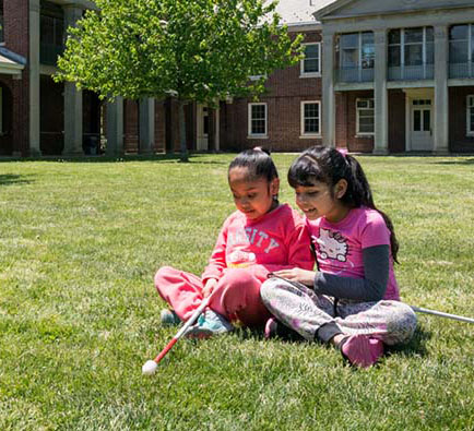 Two young girls sitting in the grass at school, white canes resting on their laps.